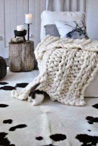 fauteuil blanc, tapis en peau de bete, petit meuble de chevet en bois, bougie, mur gris: